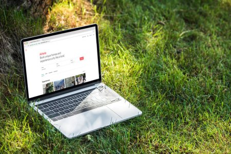 close up view of laptop with airbnb website on grass outdoors