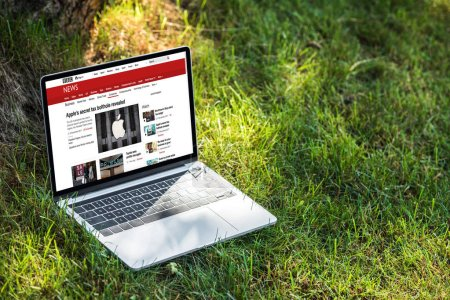 close up view of laptop with bbc news website on grass outdoors