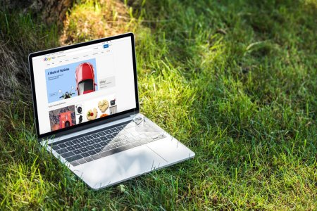 Photo for Close up view of laptop with ebay website on grass outdoors - Royalty Free Image