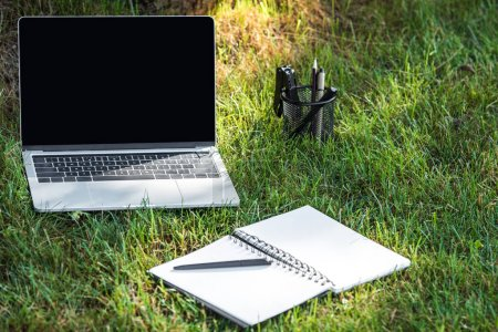 Photo for Close up view of laptop with blank screen and empty textbook with pen on grass outdoors - Royalty Free Image