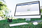 selective focus of textbook and computer with facebook website on grass outdoors