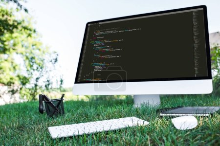 Photo for Selective focus of computer with programming language code on grass outdoors - Royalty Free Image
