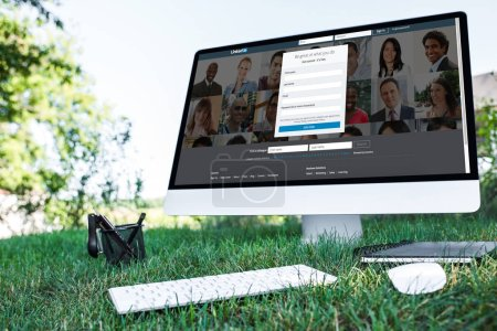 Foto de Enfoque selectivo del libro de texto y la computadora con el sitio web de linkedin en el césped al aire libre - Imagen libre de derechos