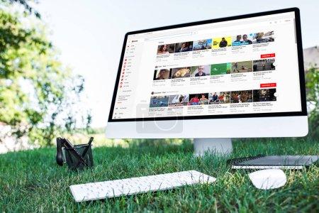 Foto de Enfoque selectivo del libro de texto y un ordenador con Web de youtube en el césped al aire libre - Imagen libre de derechos