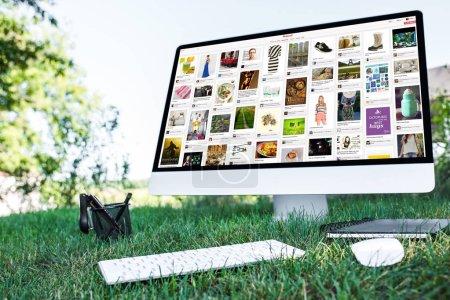 Foto de Enfoque selectivo del libro de texto y un ordenador con Web de pinterest en el césped al aire libre - Imagen libre de derechos