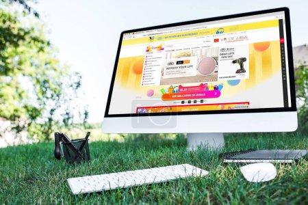 Foto de Enfoque selectivo del libro de texto y un ordenador con Web de aliexpress en el césped al aire libre - Imagen libre de derechos