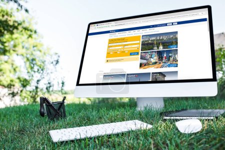 selective focus of textbook and computer with booking.com website on grass outdoors