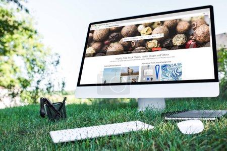 Photo pour Mise au point sélective du manuel et ordinateur avec depositphotos.com site sur l'herbe en plein air - image libre de droit