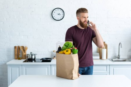 handsome bearded young man talking by smartphone and looking away in kitchen