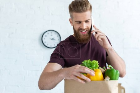 handsome smiling young man talking by smartphone and looking at grocery bag with vegetables