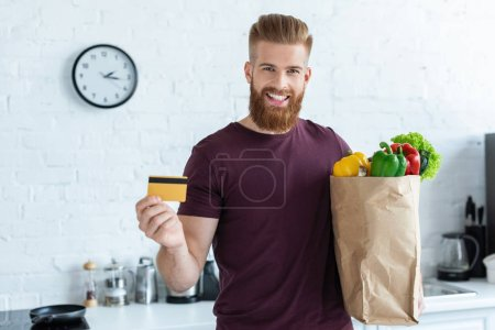 handsome bearded young man holding grocery bag with vegetables and credit card, smiling at camera in kitchen