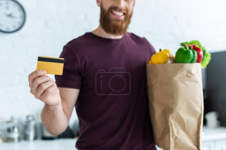 cropped shot of smiling bearded man holding credit card and grocery bag with vegetables