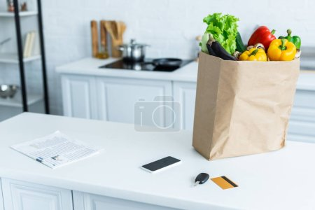 grocery bag, smartphone, newspaper, key and credit card on kitchen table