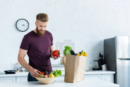 handsome young bearded man holding fresh vegetables in kitchen