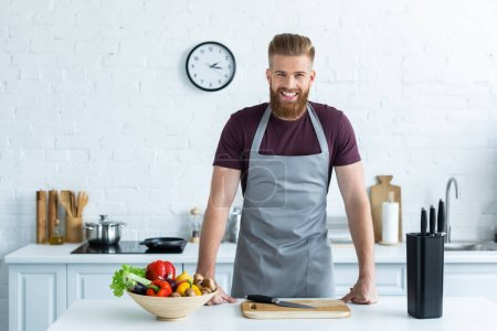 Photo for Handsome bearded young man in apron smiling at camera while cooking in kitchen - Royalty Free Image