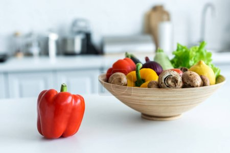 close-up view of bell pepper and bowl with fresh vegetables on kitchen table