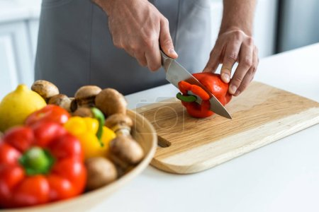 cropped shot of man cutting bell pepper on wooden cutting board