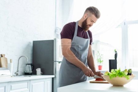 handsome bearded young man in apron cutting vegetables while cooking in kitchen