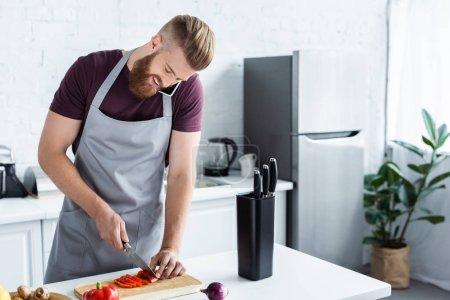 Photo pour Bel homme barbu souriant dans tablier parler par smartphone et couper des légumes dans la cuisine - image libre de droit