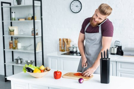 smiling bearded man in apron talking by smartphone and cutting vegetables in kitchen