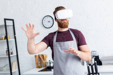 young man in apron using virtual reality headset in kitchen