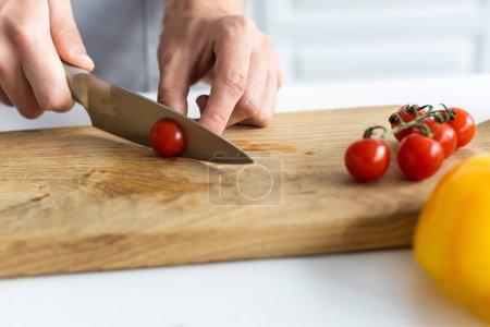 Photo pour Gros plan vue partielle des tomates-cerises coupe homme sur planche de bois - image libre de droit