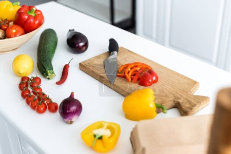 high angle view of fresh vegetables and wooden cutting board with knife on table