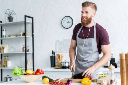 Photo for Handsome smiling bearded man in apron and earphones cooking vegetable salad in kitchen - Royalty Free Image