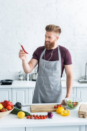 handsome smiling bearded man in apron listening music in earphones and holding chili pepper while cooking in kitchen