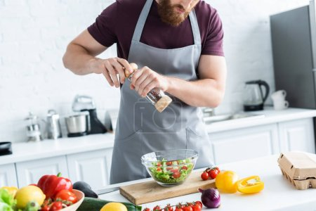 cropped shot of bearded man in apron cooking vegetable salad