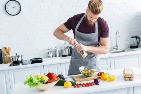 high angle view of handsome young man in apron spicing vegetable salad