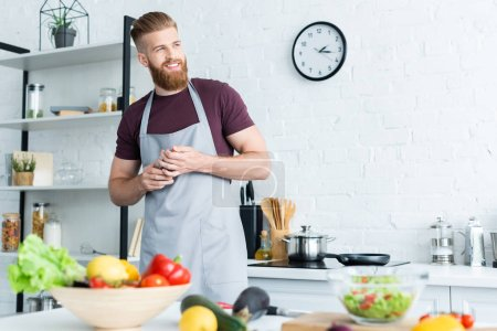 Photo for Handsome smiling bearded man in apron looking away while cooking in kitchen - Royalty Free Image
