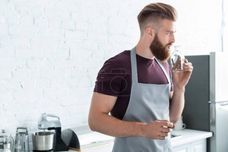 handsome bearded young man in apron holding container with cinnamon sticks in kitchen