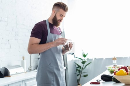 handsome bearded man in apron holding container with cinnamon sticks while cooking in kitchen