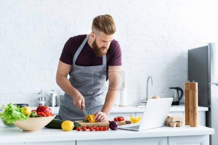 Photo pour Bel homme barbu dans tablier en utilisant ordinateur portable et cuisine salade de légumes - image libre de droit