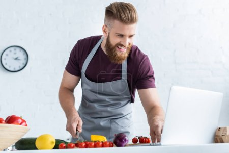 handsome smiling bearded man in apron using laptop and cooking vegetable salad