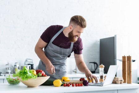 Photo for Smiling bearded man in apron using laptop and cooking vegetable salad - Royalty Free Image