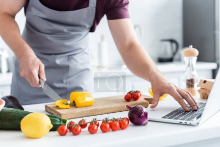 cropped shot of man in apron using laptop and cutting vegetables