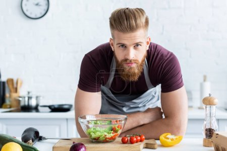 handsome bearded man in apron cooking vegetable salad and looking at camera