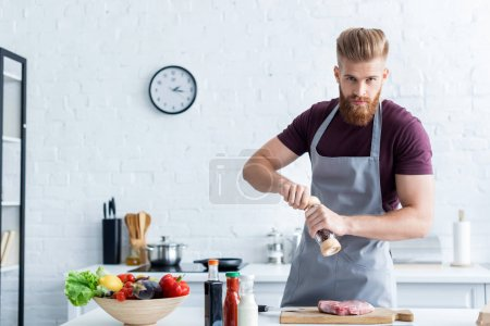 handsome bearded man in apron cooking delicious steak and looking at camera