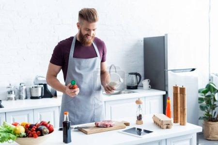 Photo pour Bel homme barbu souriant dans tablier cuisine délicieux steak dans la cuisine - image libre de droit
