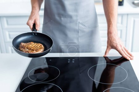 cropped shot of man in apron holding frying pan with delicious steak