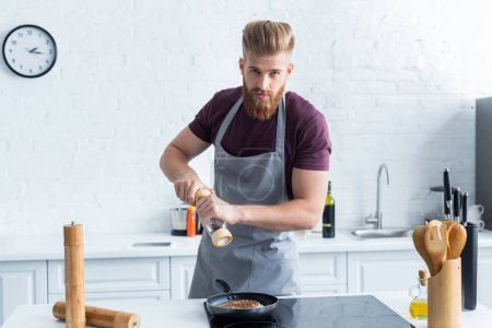 man holding pepper mill while cooking delicious steak and looking at camera