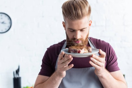 handsome bearded young man in apron holding plate with delicious beef steak