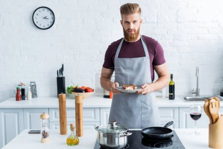 handsome bearded young man in apron holding delicious beef steak on plate and looking at camera