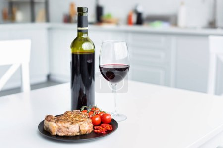 Photo for Delicious grilled steak with vegetables on plate and red wine on table - Royalty Free Image