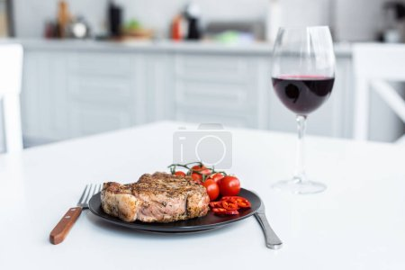 Photo for Delicious steak with cherry tomatoes on plate and glass of red wine on table - Royalty Free Image
