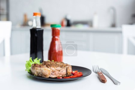 Photo for Delicious grilled steak, sauces and fork with knife on table - Royalty Free Image