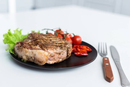 Photo for Close-up view of delicious grilled steak with lettuce, pepper and cherry tomatoes on black plate - Royalty Free Image