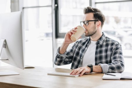 young man in eyeglasses drinking coffee from paper cup and using desktop computer